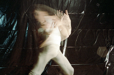 long exposure of a young Ahasiw dancing against a black tarp